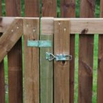 Toggle latch in use to keep brown color wooden fence door locked